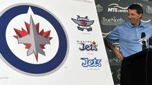 Winnipeg Jets owner Mark Chipman looks at the NHL team's new logo at a news conference in Winnipeg, July 22, 2011. REUTERS/Fred Greenslade (FRED GREENSLADE)