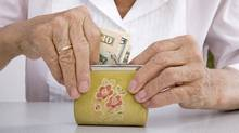 older woman puts American money in a coin purse (Photos.com)