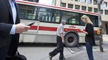 Cellphone users cross Bay street in Toronto's financial district. (Gloria Nieto/The Globe and Mail)