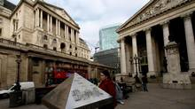 A tourist looks at a map in London. On Friday, Oxford Properties said it would buy a landmark London shopping centre located in the Royal Exchange, pictured on the right. (MAX NASH/AP)