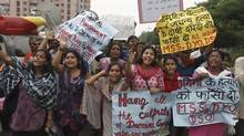 Indians hold placards as they shout slogans seeking death sentence for the juvenile convict who was earlier given a three year term in a reform home, after a judge pronounced death sentence for four others convicted in the rape and murder of a student on a moving New Delhi bus last year. (Altaf Qadri/Associated Press)