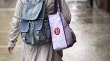A woman carries a shopping bag with the Lululemon Athletica Inc logo outside one of the company's stores in New York, March 19, 2013. (LUCAS JACKSON/REUTERS)
