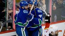 Vancouver Canucks' Yannick Weber, left, of Switzerland, and Tom Sestito celebrate Weber's goal as Calgary Flames' Brian McGrattan, right, looks on during third period NHL action in Vancouver, B.C., on Saturday March 8, 2014. (DARRYL DYCK/THE CANADIAN PRESS)