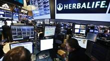 Traders work at the post that trades Herbalife stock on the floor of the New York Stock Exchange (BRENDAN MCDERMID/REUTERS)