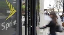 A customer enters a Sprint store in Chicago. The company posted a quarterly loss of $1.32-billion (U.S.) compared with a loss of $1.30-billion in the year-ago quarter. (M. Spencer Green/The Associated Press)