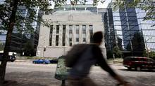 A bicyclist rides past the Bank of Canada building in Ottawa, Ontario, Canada, on Thursday, June 13, 2013. (Patrick Doyle/Bloomberg)
