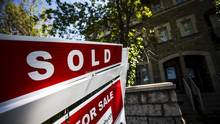A 'For Sale' sign stands in front of a home that has been sold in Toronto. (© Mark Blinch / Reuters)