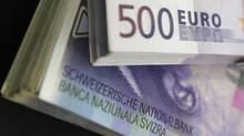 Stacks of Swiss franc and Euro banknotes are displayed in a bank in Bern August 15, 2011. (PASCAL LAUENER/Reuters)