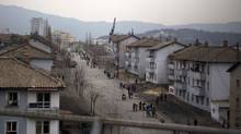 North Koreans walk bicycles along a street in the residential district of Kaesong, North Korea, north of the demilitarized zone which separates the two Koreas, Tuesday, April 23, 2013. (AP Photo/David Guttenfelder) (David Guttenfelder/AP)