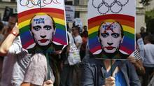 "Activists holding placards depicting Russian President Vladimir Putin, participate at a protest against Russia's new law on gays, in central London, on Aug. 10, 2013. Hundreds of protesters called for the Winter 2014 Olympic Games to be taken away from Sochi, Russia, because of a new Russian law that bans ""propaganda of nontraditional sexual relations"" and imposes fines on those holding gay pride rallies. (Lefteris Pitarakis/AP)"