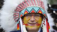 "Canadian Prime Minister Stephen Harper smiles while wearing his tradition native head dress after becoming ""Chief Speaker"" at a Kainai Chieftainship ceremony on the Blood Indian reserve in Stand Off, Alberta, July 11, 2011. (Todd Korol/Reuters)"