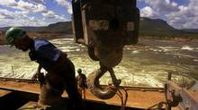 An unidentified worker handles the hook of a crane during the construction of the Luis Eduardo Magalhaes hydro-electric plant, in the city of Lajeado, in the northern state of Tocantins, Brazil Friday June 1, 2001. (Dado Galdieri/AP/Dado Galdieri/AP)