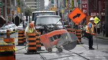 Construction work at the intersection of Dundas St. West and Spadina Ave. on July 15 2014. Traffic lanes have been reduced to single lanes in all directions and busses are running on the Spadina route instead of streetcars. The work is expected to be complete by the end of August this year. (Fred Lum/The Globe and Mail)