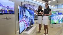 In this Feb. 20, 2014 file photo, models pose with a Samsung Electronics curved UHD TV during a press unveiling at its headquarters in Seoul, South Korea. (Ahn Young-joon/AP)