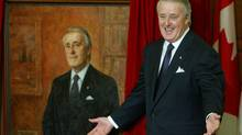 Former Prime Minister Brian Mulroney greets the unveiling of his official portrait in 2002, which includes a family photo in the background. (TOM HANSON)
