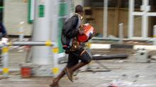 Looters flee with their ware as riots sweep Malawi's commercial capital Blantyre in this 2004 file photo. President Bingu wa Mutharika has become increasingly intolerant of dissent. (Salim Henry/REUTERS/Salim Henry/REUTERS)