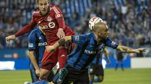 Toronto FC's Alvaro Rey leaps onto Montreal Impact's Marco Di Vaio during first half Voyageurs Cup action Wednesday, June 4, 2014 in Montreal. THE CANADIAN PRESS/Paul Chiasson (Paul Chiasson/THE CANADIAN PRESS)