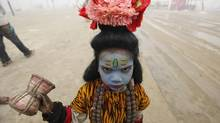 An Indian child dressed as Hindu god Shiva to seek alms reacts to camera at Sangam, the confluence of the rivers Ganges and Yamuna during the Maha Kumbh festival in Allahabad, India. (Rajesh Kumar Singh/AP)