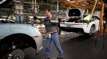 Workers at the General Motors Oshawa assembly plant work on the Camaro model Aug 22, 2013. (Moe Doiron/The Globe and Mail)
