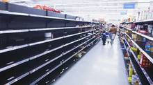 A woman and child walk through an aisle, emptied in preparation for Hurricane Sandy, in a Wal-Mart store in Riverhead, New York, Oct. 28, 2012. (Lucas Jackson/REUTERS)