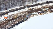 In this aerial photo, crews work the scene of a train derailment Wednesday, Jan. 27, 2016, along Hwy. 26 south of Brownsville, Minn. Authorities say two of six derailed train cars have broken through the ice on the Mississippi River in southeastern Minnesota. (Erik Daily/La Crosse Tribune via AP)