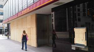 A woman walks by a boarded-up CIBC branch at College St. and Yonge St. on Sunday morning after G20 protesters smashed the windows on Saturday.
