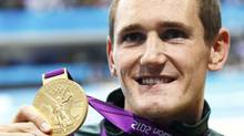 Cameron van der Burgh of South Africa holds his gold medal during the men's 100m breaststroke victory ceremony at the London 2012 Olympic Games at the Aquatics Centre July 29, 2012. (MICHAEL DALDER/REUTERS)