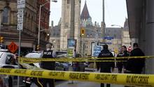 Police stand behind police tape after a RCMP officer was found shot dead in a building below Parliament Hill, in Ottawa on Thursday, March 17, 2016. (Fred Chartrand/THE CANADIAN PRESS)