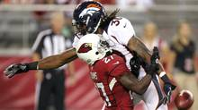 Arizona Cardinals punt returner Michael Adams, left, is bowled over by Denver Broncos' David Bruton, right, who was penalized for interfering with catch in the fourth quarter of a preseason NFL football game Thursday, Aug. 30, 2012, in Glendale, Ariz. (Associated Press)