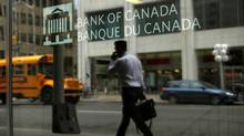A man is reflected in a window while walking past the Bank of Canada office in Ottawa. (CHRIS WATTIE/Reuters)