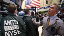 Specialist Traders wear jackets with the ticker symbol for TD Ameritrade to celebrate the transfer of the company's stock to the New York Stock Exchange, April 25, 2012. (BRENDAN MCDERMID/REUTERS)