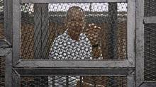 In this May 3, 2014 file photo, Al-Jazeera's award-winning Australian correspondent Peter Greste appears in a defendants' cage in the Police Academy courthouse along with several other defendants during a trial on terror charges in Cairo, Egypt. (Hamada Elrasam/AP)