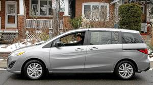 John Heinzl takes his 8-year-old son Curtis to hockey while reviewing a 2012 Mazda5.