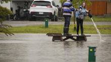 A teenager pours water out of her boot after wading through flood waters in a park in Claresholm, Alta., on June 18, 2014. (JEFF McINTOSH/THE CANADIAN PRESS)