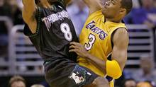 The Minnesota Timberwolves' Latrell Sprewell, left, and the Los Angeles Lakers' Devean George battle for possession in the first quarter of Game 4 of the Western Conference Finals in Los Angeles, May 27, 2004. (KEVORK DJANSEZIAN/The Associated Press)