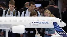 Visitors look at an A350 aircraft miniature at the EADS booth during the ILA Berlin Air Show in Selchow, south of Berlin, on Sept. 13, 2012. (TOBIAS SCHWARZ/REUTERS)