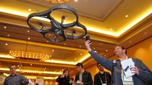 An attendee photographs an A.R. Drone helicopter by Parrot as it flies overhead during a press event for the 2010 International Consumer Electronics Show January 5, 2010 in Las Vegas, Nevada. The device, which is controlled wirelessly from an iPhone, is expected to be available in late 2010, and has two cameras on it making it useful for video game applications. CES, the world's largest annual consumer technology tradeshow, runs from January 7-10. AFP PHOTO / Robyn Beck (Photo credit should read ROBYN BECK/AFP/Getty Images) (ROBYN BECK/AFP/Getty Images)