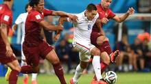 United States' Clint Dempsey, centre, is challenged by Portugal's Bruno Alves, left, and Portugal's Miguel Veloso, right, during the group G World Cup soccer match between the USA and Portugal at the Arena da Amazonia in Manaus, Brazil, Sunday, June 22, 2014. (Paulo Duarte/AP)
