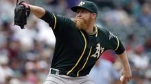 "Oakland Athletics reliever Sean Doolittle throws against the Seattle Mariners in the ninth inning of a baseball game on Sunday, July 13, 2014, in Seattle. The Athletics are ""off the charts"" with the best record in baseball and yet they have a payroll that is in the lowest quintile of the league. (ELAINE THOMPSON/THE ASSOCIATED PRESS)"