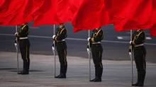 Soldiers of the People's Liberation Army's guard of honour hold flags in front of Beijing's Tiananmen Square during the official welcoming ceremony for Serbian President Tomislav Nikolic outside the Great Hall of the People in Beijing August 26, 2013. Nikolic is on a five-day visit to China. REUTERS/Petar Kujundzic (CHINA - Tags: POLITICS MILITARY TPX IMAGES OF THE DAY) (PETAR KUJUNDZIC/Reuters)