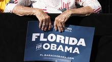 A senior citizen holds a sign as she listens to Barack Obama speak during a campaign rally in Delray, Florida, October 23, 2012. (Kevin Lamarque/Reuters)