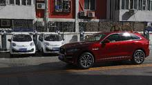 A SUV vehicle drives past electric cars parked at a charging station outside a residential building in Beijing, April 14, 2017. (Andy Wong/AP)