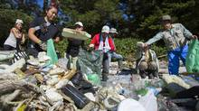 Japanese delegates sort through garbage some of which is possibly tsunami debris on beach on Wouwer Island near Ucluelet, BC September 26, 2013 to investigate the tsunami debris issue in B.C. (John Lehmann/The Globe and Mail)