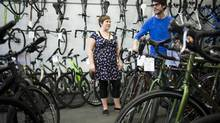 Tom Woywitka of Bikes on the Drive helps Michelle Kangro as she browses for a new bicycle in Vancouver on April 1, 2013. Starting today the purchase of bicycles only include GST. (Rafal Gerszak for The Globe and Mail)