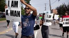 Aaron Coleman, left, joins other protesters marching on Florissant Road in historic downtown Ferguson, Mo., Monday, Aug. 11, 2014. The group marched along the closed street, rallying in front of the town's police headquarters to protest the shooting of 18-year-old Michael Brown by Ferguson police officers. Brown, who was killed in a confrontation with police in the St. Louis suburb, was shot Saturday, Aug. 9, 2014, and died following the confrontation with police. (Sid Hastings/AP)