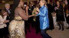 South African jazz singer Judith Sephuma, left, invites U.S. Secretary of State Hillary Rodham Clinton to dance with her to African music at a gala dinner hosted by South Africa's Foreign Minister Maite Nkoana-Mashabane in Pretoria, South Africa, on Aug. 7, 2012. (Jacquelyn Martin/AP)
