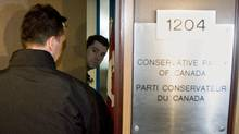 An unidentified staffer opens the door for a plainclothes RCMP officer during a raid on Conservative Party headquarters in Ottawa on April 15, 2008. (Tom Hanson/THE CANADIAN PRESS)