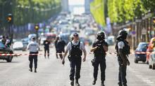 Police officers and anti-riot police officers patrol the Champs-Elysees in Paris on June 19, 2017. (ALAIN JOCARD/AFP/Getty Images)