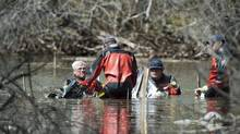 Members of an RCMP underwater recovery team search Sunday May 12, 2012, at the site where one of two planes crashed Saturday near St. Brieux, Sask. (Liam Richards/THE CANADIAN PRESS)