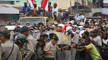 Indonesian police (L) clash with striking workers (R) of US gold and copper mining giant company Freeport McMoran in Timika in Indonesia's Papua province. (TJAHJO ERANIUS/AFP/Getty Images)